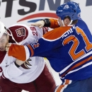 Phoenix Coyotes' Jordan Szwarz (29) fights Edmonton Oilers' Andrew Ference (21) during third period NHL hockey action in Edmonton, Alberta, on Tuesday, Dec. 3, 2013 The Associated Press