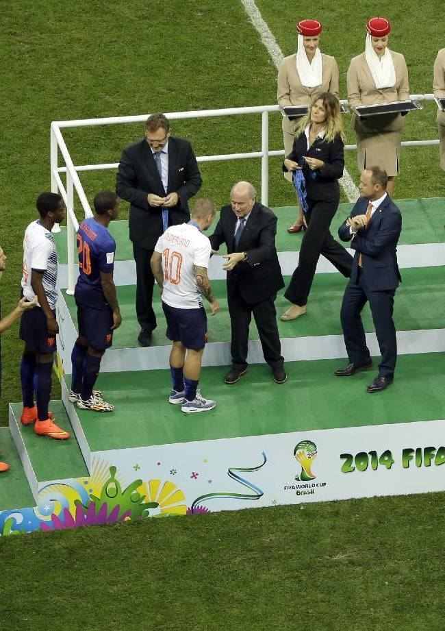 Dutch players get their medals from Fifa President, Sepp Blatter, center, after the World Cup third-place soccer match between Brazil and the Netherlands at the Estadio Nacional in Brasilia, Brazil, Saturday, July 12, 2014. Robin van Persie and Daley Blind scored early goals to help give the Netherlands a 3-0 win over host Brazil in the third-place match at the World Cup on Saturday