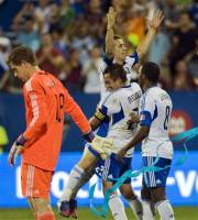 Montreal Impact's Felipe Martins is held up by teammates Davy Arnaud (22) and Patrice Bernier after scoring against Philadelphia Union's goaltender Zac MacMath, left, during second half MLS soccer action in Montreal, Saturday, Aug. 4, 2012. (AP Photo/The Canadian Press,Graham Hughes)