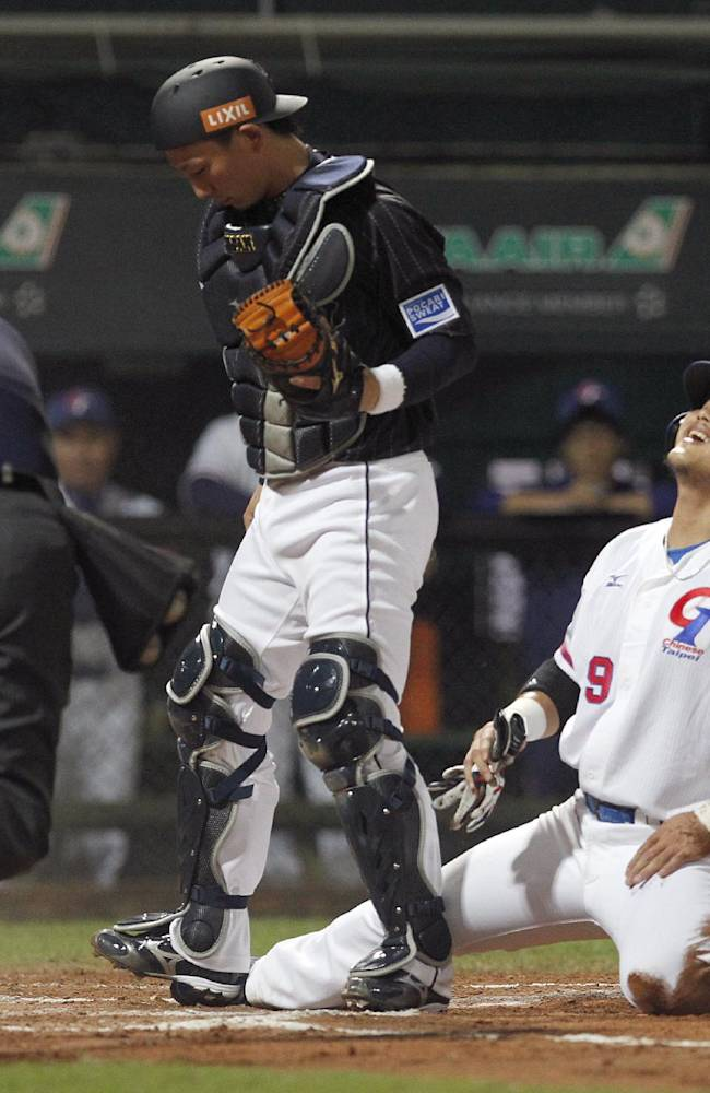 Taiwan's Chen Chun-hsiu is called out after being tagged by Japan's catcher Motohiro Shima, center, in the first inning of their exhibition baseball game at the Xinzhuang Baseball Stadium in New Taipei City, Taiwan, Friday, Nov. 8, 2013