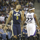 Utah Jazz guard Trey Burke, left, grimaces as he walks past Sacramento Kings guard Isaiah Thomas, after injuring his ankle during the third quarter of an NBA basketball game in Sacramento, Calif., Wednesday, Dec. 11, 2013. Burke left the game but was ab