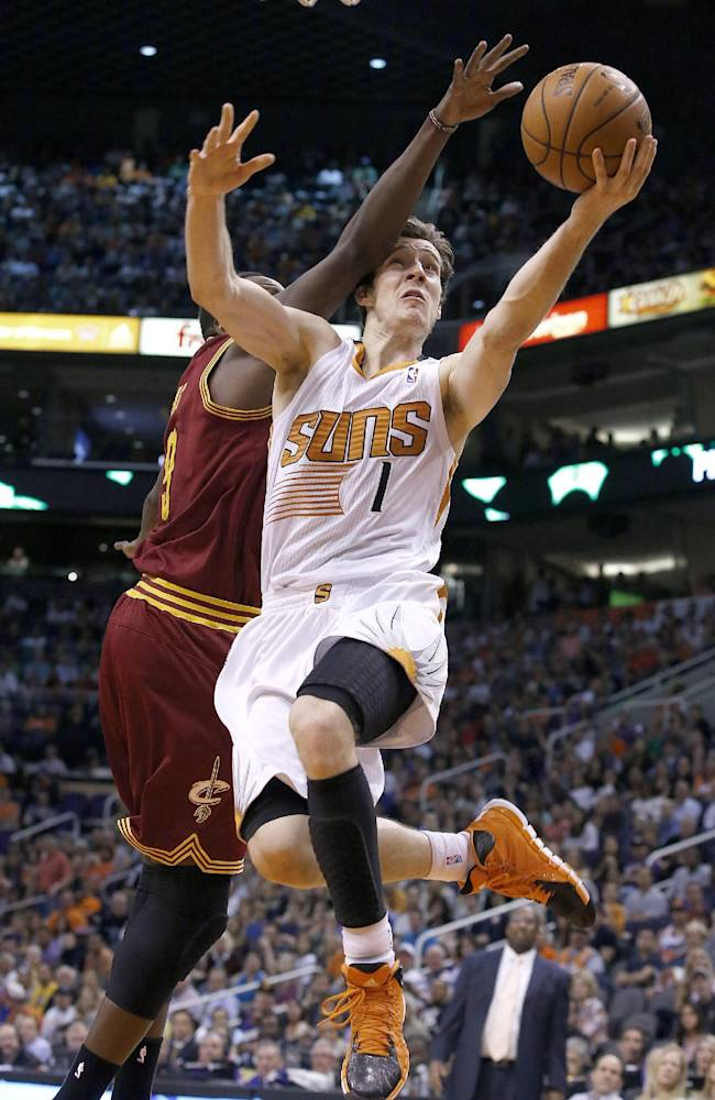 Cleveland Cavaliers' Luol Deng (9), of Sudan, fouls Phoenix Suns' Goran Dragic (1), of Slovenia, as he goes up for a shot during the second half of an NBA basketball game, Wednesday, March 12, 2014, in Phoenix.  The Cavaliers defeated the Suns 110-101