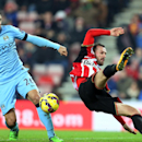 Sunderland's Steven Fletcher, right, vies for the ball with Manchester City's Martin Demichelis, during their English Premier League soccer match at the Stadium of Light, Sunderland, England, Wednesday, Dec. 3, 2014