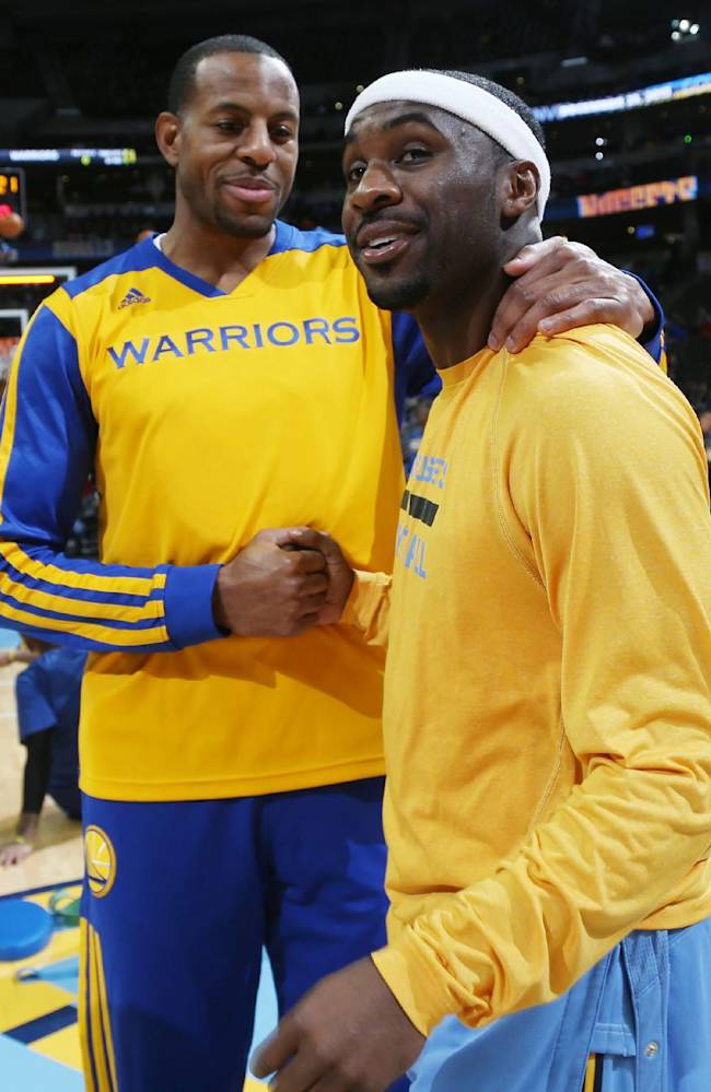 Golden State Warriors guard Andre Iguodala, left, greets former teammate and Denver Nuggets guard Ty Lawson at center court as the teams warm up for an NBA basketball game in Denver, Monday, Dec. 23, 2013. Iguodala was making his first appearance in Denver since being traded to Golden State in the off-season