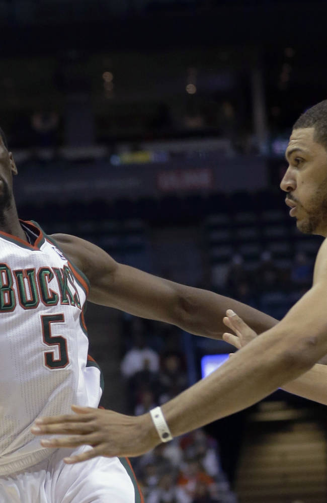 Milwaukee Bucks' Ekpe Udoh goes after a ball in front of San Antonio Spurs' Jeff Ayres during the first half of an NBA basketball game Wednesday, Dec. 11, 2013, in Milwaukee