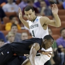 Pacific's Sama Taku tries to drive past Miami's Trey McKinney Jones (4) during the first half of a second-round game of the NCAA college basketball tournament Friday, March 22, 2013, in Austin, Texas. (AP Photo/David J. Phillip)