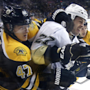 Boston Bruins defenseman Torey Krug (47) grapples with Pittsburgh Penguins right wing Craig Adams (27) along the boards during the third period of an NHL hockey game in Boston, Monday, Nov. 25, 2013. The Bruins won 4-3 in overtime The Associated Press