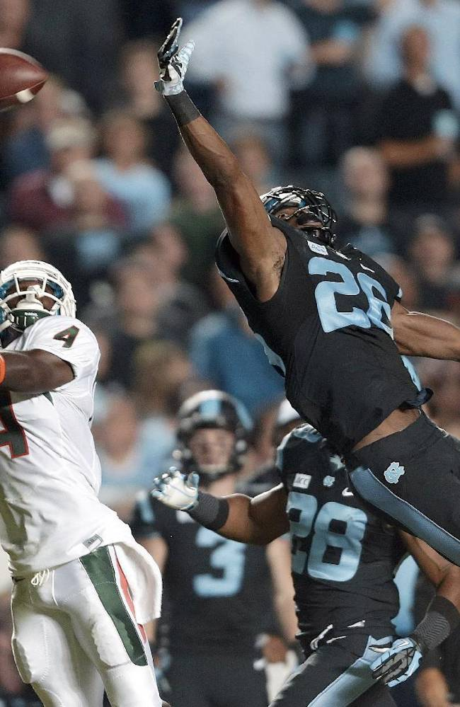 Miami's Phillip Dorsett (4) reaches for a pass as North Carolina's Dominique Green (26) defends during the first half of an NCAA college football game in Chapel Hill, N.C., Thursday, Oct. 17, 2013. The pass was complete