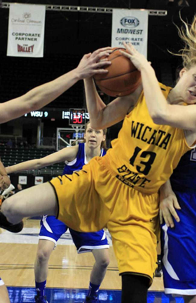 Wichita State's Kelsey Jacobs, center, heads to the basket as Drake's Kyndal Clark, left, and Liza Heap defend during the first half of an NCAA college basketball game in the championship of the Missouri Valley Conference women's tournament on Sunday, March 16, 2014, in St. Charles