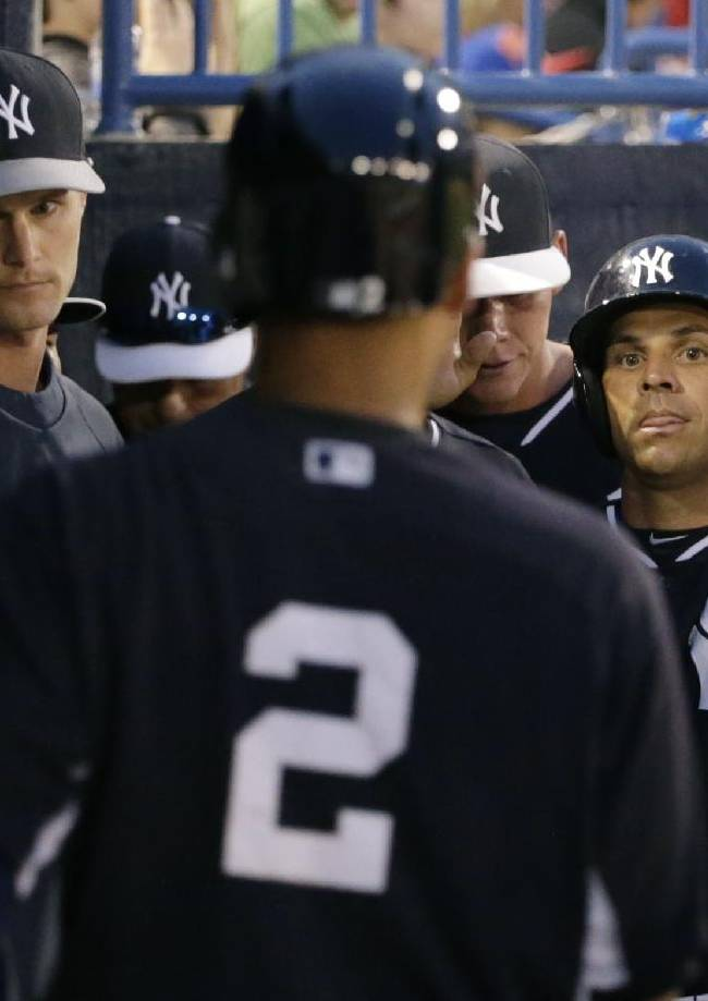 New York Yankees congratulate Brian Roberts after he scored on Derek Jeter's second-inning ground out in a spring exhibition baseball game against the Pittsburgh Pirates in Tampa, Fla., Friday, March 21, 2014