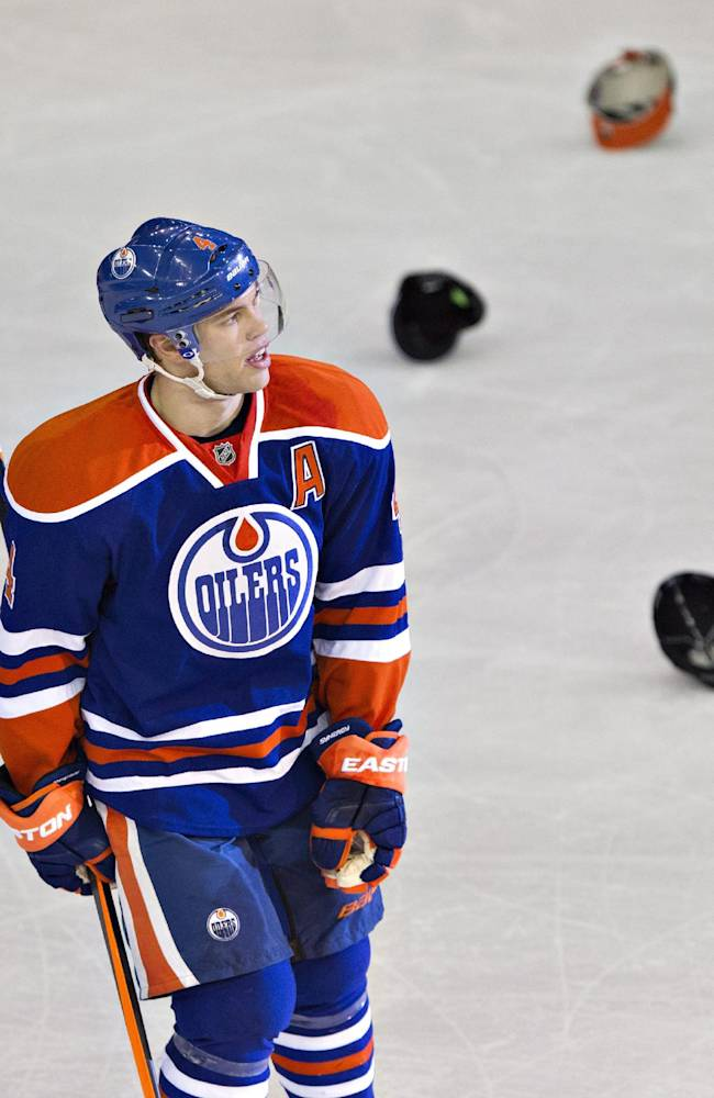 Edmonton Oilers' Taylor Hall (4) reacts after scoring a hat trick and fans throw their hats onto the ice surface during third period NHL hockey action in Edmonton, Alberta, Thursday, Dec. 5, 2013