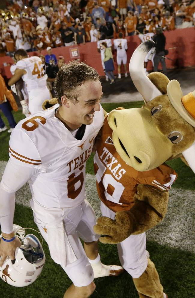 FILE- In this Oct. 3, 2013, file photo, Texas quarterback Case McCoy celebrates with the team mascot after their 31-30 win over Iowa State in an NCAA college football game in Ames, Iowa. McCoy carries himself with the swagger of a national championship-winning quarterback, not a career backup. It's that natural-born confidence that let him step in for injured David Ash and lead the Longhorns to three consecutive victories