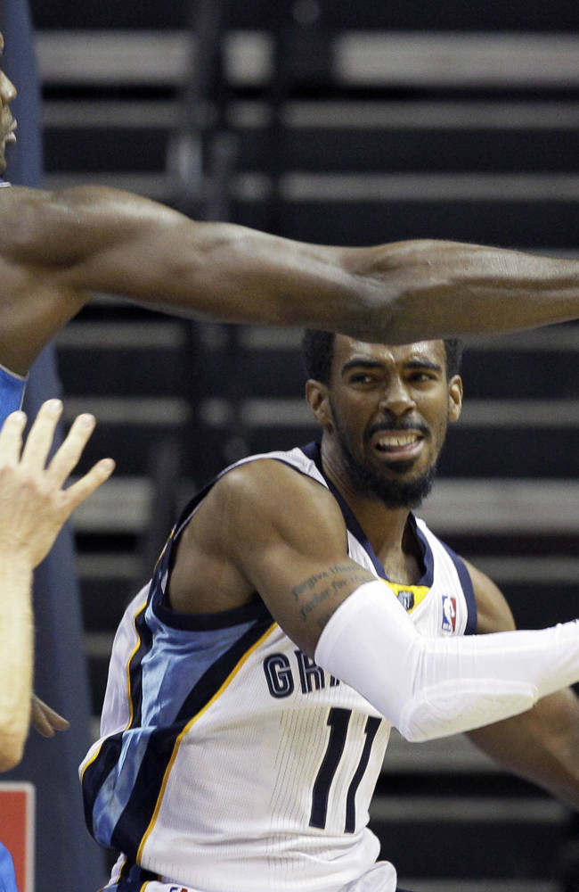 Memphis Grizzlies' Mike Conley (11) tries to pass the ball around Dallas Mavericks' Samuel Dalembert (1) during the first half of an NBA preseason basketball game in Memphis, Tenn., Wednesday, Oct. 9, 2013