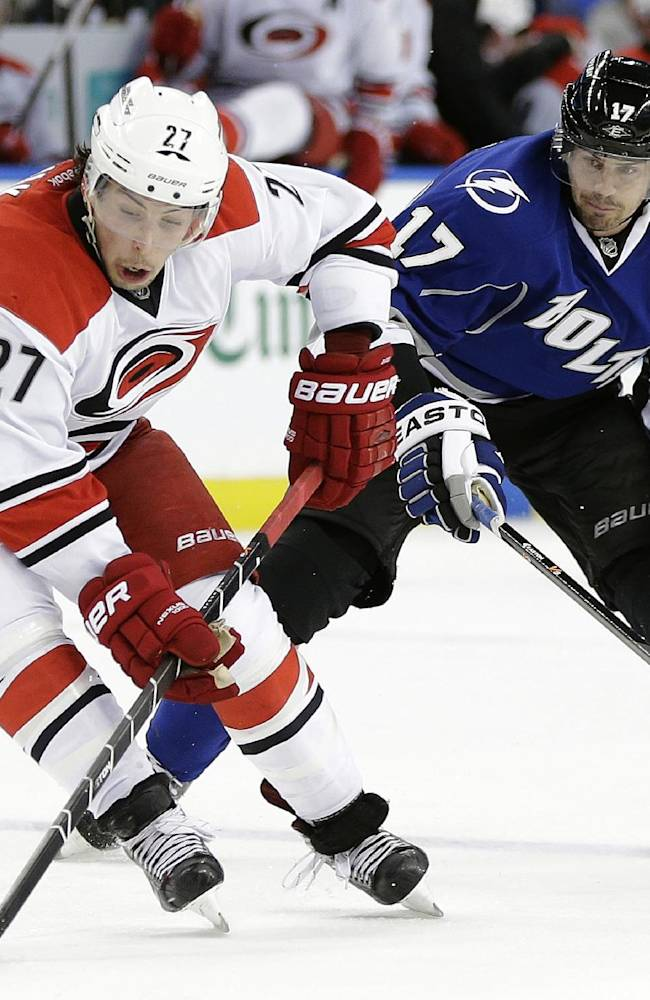 Carolina Hurricanes defenseman Justin Faulk (27) maneuvers around Tampa Bay Lightning center Alex Killorn (17) during the second period of an NHL hockey game, Saturday, Dec. 21, 2013, in Tampa, Fla