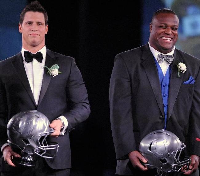 Houston Texans linebacker Brian Cushing, left, and Indianapolis Colt defensive end Cory Redding accept their Ed Block Courage Awards at a banquet in Baltimore Monday, March 17, 2014. The award, named for the late former trainer of the Baltimore Colts, recognizes a player from each team in the National Football League who has displayed courage in the face of adversity over the past year