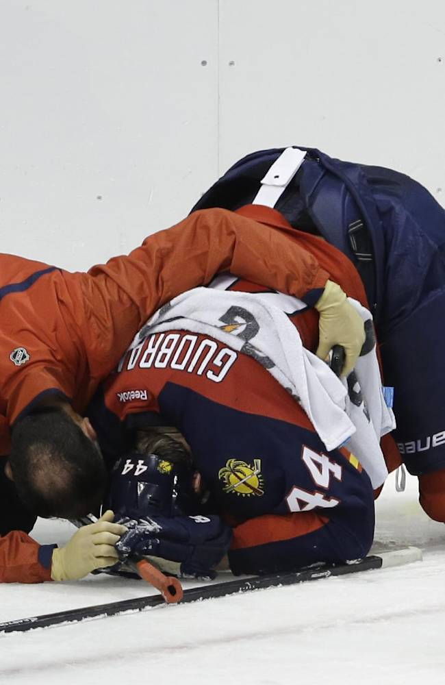 A trainer talks with Florida Panthers defenseman Erik Gudbranson (44) after he fell to the ice in the second period during a preseason NHL hockey game against the Tampa Bay Lightning, Saturday, Sept. 28, 2013, in Sunrise, Fla