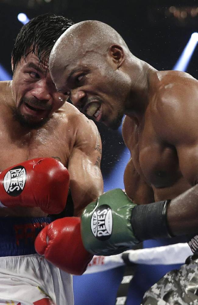 Manny Pacquiao, left, of the Philippines, trades blows with Timothy Bradley, in their WBO welterweight title boxing fight Saturday, April 12, 2014, in Las Vegas. Pacquiao won the bout by unanimous decision