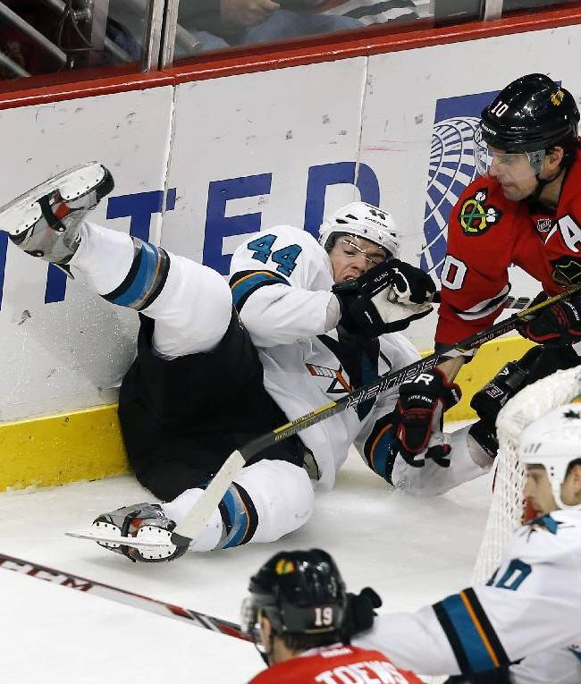 San Jose Sharks defenseman Marc-Edouard Vlasic (44) and Chicago Blackhawks left wing Patrick Sharp (10) hit the ice while battling for the puck during the third period of an NHL hockey game on Sunday, Nov. 17, 2013, in Chicago