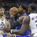 New York Knicks' Carmelo Anthony (7) drives to the basket as Utah Jazz's Marvin Williams (2) and Enes Kanter (0) defend in the first quarter during an NBA basketball game Monday, March 31, 2014, in Salt Lake City The Associated Press