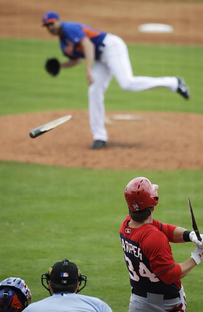 Washington Nationals' Bryce Harper, right, breaks his bat on a ground out off New York Mets pitcher John Lannan, top, in the third inning of an exhibition spring training baseball game, Thursday, March 27, 2014, in Port St. Lucie, Fla
