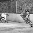 In this March 5, 1954, file photo, Toronto Maple Leaf's Tim Horton, right, outmaneuvers Detroit Red Wings' Tony Leswick (8) who falls to the ice during the first period of an NHL hockey game in Detroit. Few things unite Canadians the way Tim Hortons does.