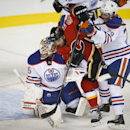 Edmonton Oilers goalie Viktor Fasth, left, has Calgary Flames Devin Setoguchi, center, checked into him by teammate Dillon Simpson during the first period of an NHL preseason hockey game in Calgary, Alberta, Sunday, Sept. 21, 2014 The Associated Press