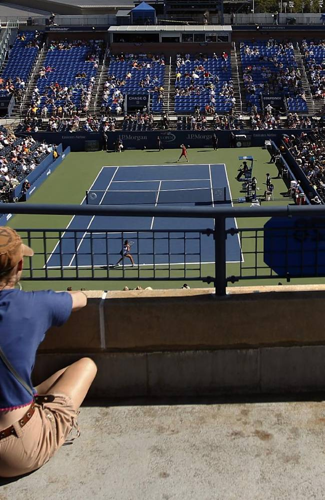 A spectator watches play from an upper walkway at Louis Armstrong Stadium during the second round of the 2014 U.S. Open tennis tournament, Thursday, Aug. 28, 2014, in New York