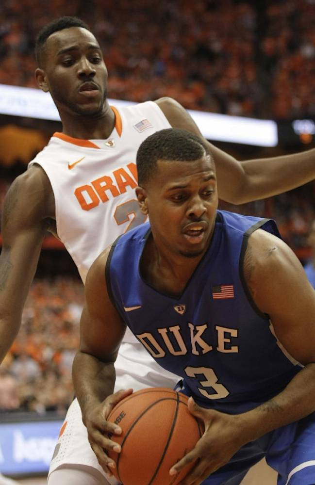 Duke's Tyler Thornton (3) looks to pass the ball under pressure from Syracuse's Rakeem Christmas in the first half of an NCAA college basketball game in Syracuse, N.Y., Saturday, Feb. 1, 2014