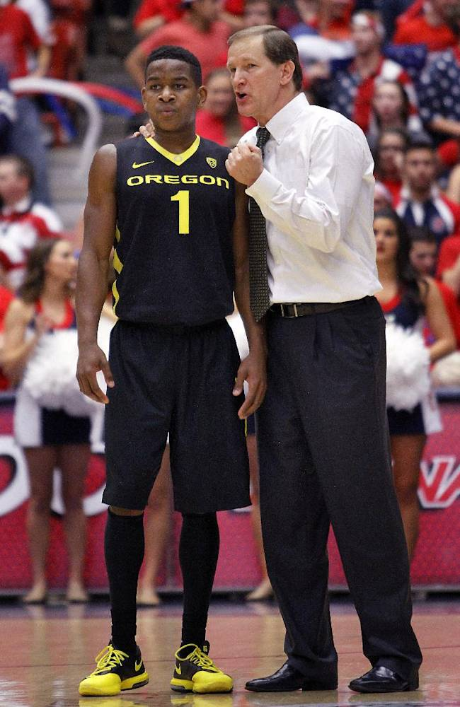 Oregon coach Dana Altman, right, talks to one of his players, Dominic Artis (1), during an Arizona foul shot in the second half of an NCAA college basketball game Thursday, Feb. 6, 2014, in Tucson, Ariz. Arizona won 67-65