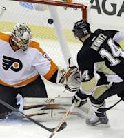 Pittsburgh Penguins' Chris Kunitz (14) puts the puck behind Philadelphia Flyers goalie Ray Emery (29) in the first period of an NHL hockey game in Pittsburgh, Wednesday, Nov. 13, 2013. The goal was disallowed because the puck went in off Kunitz's skate. (AP Photo/Gene J. Puskar)