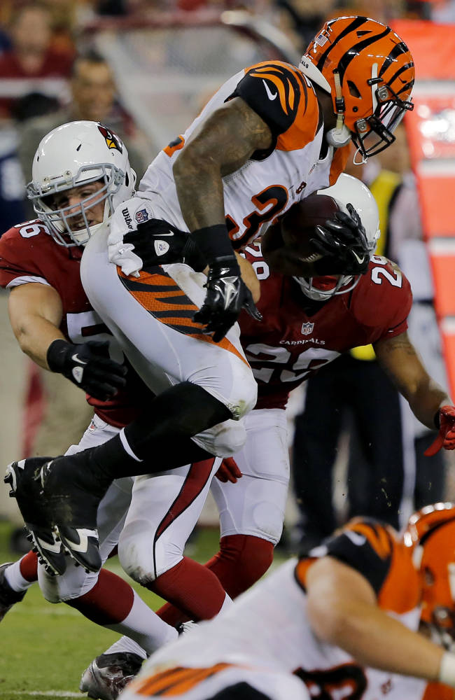 Cincinnati Bengals running back Jeremy Hill is stopped by Arizona Cardinals linebacker Glenn Carson (56) and Teddy Williams (29) during the second half of an NFL preseason football game, Sunday, Aug. 24, 2014, in Glendale, Ariz