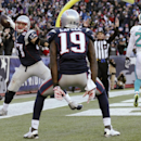 New England Patriots tight end Rob Gronkowski, left, celebrates his touchdown as wide receiver Brandon LaFell (19) watches and Miami Dolphins strong safety Reshad Jones (20) walks away in the second half of an NFL football game, Sunday, Dec. 14, 2014, in