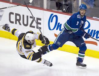 FILE - In this June 10, 2011, file photo, Boston Bruins defenseman Adam McQuaid, left, is checked to the ice by Vancouver Canucks defenseman Kevin Bieksa during the second period of Game 5 of the Stanley Cup hockey finals in Vancouver, British Columbia. The Anaheim Ducks announced Tuesday, June 30, 2015, they have acquired veteran defenseman Bieksa from the Canucks for a second-round pick in the 2016 draft. (/Jonathan Hayward/The Canadian Press via AP, File)