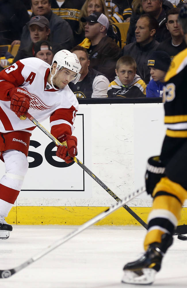 Detroit Red Wings' Pavel Datsyuk lets go a shot as Boston Bruins defenseman Zdeno Chara (33) defends during the third period of Detroit's 1-0 win in Game 1 of a first-round NHL playoff hockey series, in Boston on Friday, April 18, 2014