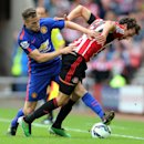 Manchester United's Tom Cleverley, left, vies for the ball with Sunderland's Will Buckley, right, during their English Premier League soccer match at the Stadium of Light, Sunderland, England, Sunday, Aug. 24, 2014
