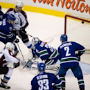 Colorado Avalanche's Paul Stastny (26) scores against Vancouver Canucks goalie Jacob Markstrom, center, of Sweden, as Canucks' Daniel Sedin (22), of Sweden; Yannick Weber (6), of Switzerland; Dan Hamhuis (2) and Henrik Sedin (33), of Sweden, and Colorado'