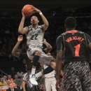 Georgetown's Otto Porter Jr. (22) goes up as Cincinnati's Cashmere Wright (1) looks on during the first half of an NCAA college basketball game at the Big East Conference tournament, Thursday, March 14, 2013 in New York. Georgetown won 62-43. (AP Photo/Mary Altaffer)