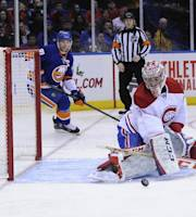 Montreal Canadiens goalie Carey Price deflects the puck as New York Islanders center John Tavares (91) skates behind in the second period of an NHL hockey game at Nassau Coliseum in Uniondale, N.Y., Saturday, Dec. 14, 2013. (AP Photo/Kathleen Malone-Van Dyke)