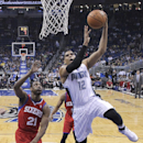 Orlando Magic's Tobias Harris (12) makes a basket as he gets past Philadelphia 76ers' Thaddeus Young (21) during the first half of an NBA basketball game in Orlando, Fla., Sunday, March 2, 2014 The Associated Press