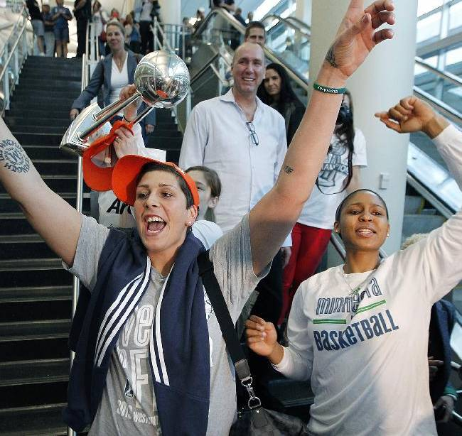 Minnesota Lynx's Janel McCarville, left, and Maya Moore, are welcomed by fans at the Humphrey Terminal, Friday, Oct. 11, 2013, in Bloomington, Minn. The Lynx won their second WNBA title in three years beating the Atlanta Dream 86-77 on Thursday