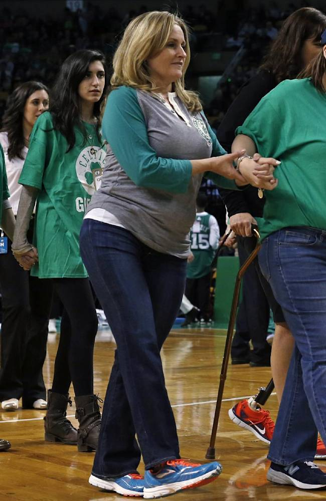 Survivors who were injured in the 2013 Boston Marathon bombings walk hand-in-hand onto the floor of the TD Garden to be honored during a break in an NBA basketball game between the Boston Celtics and the Washington Wizards in Boston, Wednesday, April 16, 2014. At left are Celeste Corcoran, and her daughter, Sydney, and at center, Roseann Sdoia walks with Erika Brannock, right