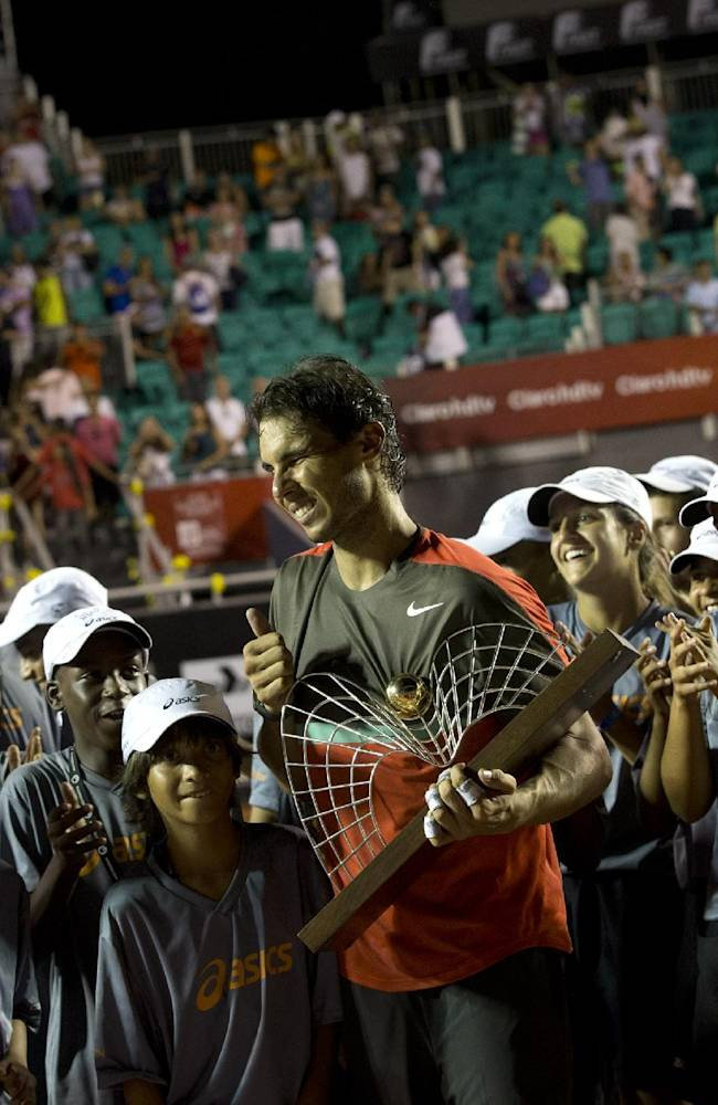 Ball boys and girls applaud Rafael Nadal as he holds his trophy after winning the Rio Open tennis tournament in Rio de Janeiro, Brazil, Sunday, Feb.23, 2014. Rafael Nadal returned from a troublesome back injury to win the Rio Open on Sunday, defeating Alexandr Dolgopolov 6-3, 7-6