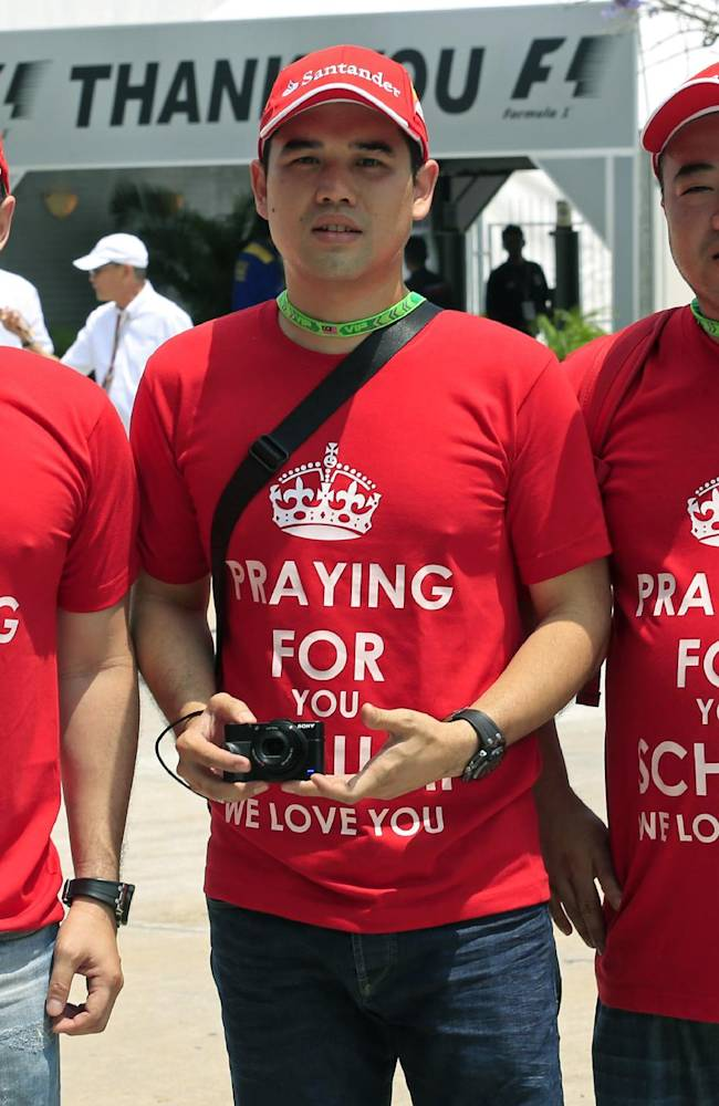 Fans of former Formula One driver Michael Schumacher of Germany wear t-shirts printed with well-wishes before the Malaysian Formula One Grand Prix at Sepang International Circuit in Sepang, Malaysia, Sunday, March 30, 2014