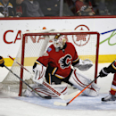Buffalo Sabres' Drew Stafford (14) scores past Calgary Flames goalie Joni Ortio, of Finland, as Flames' Mark Giordano (5) defends during first period NHL hockey action in Calgary, Alberta, on Tuesday March 18, 2014 The Associated Press