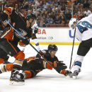 Anaheim Ducks' Clayton Stoner, left and Ben Lovejoy vie with San Jose Sharks' Tomas Hertl (48) for control of the puck during the third period of a preseason NHL hockey game in Anaheim, Calif., on Saturday, Oct. 4, 2014. (The Ducks won 2-1. AP Photo/Chris