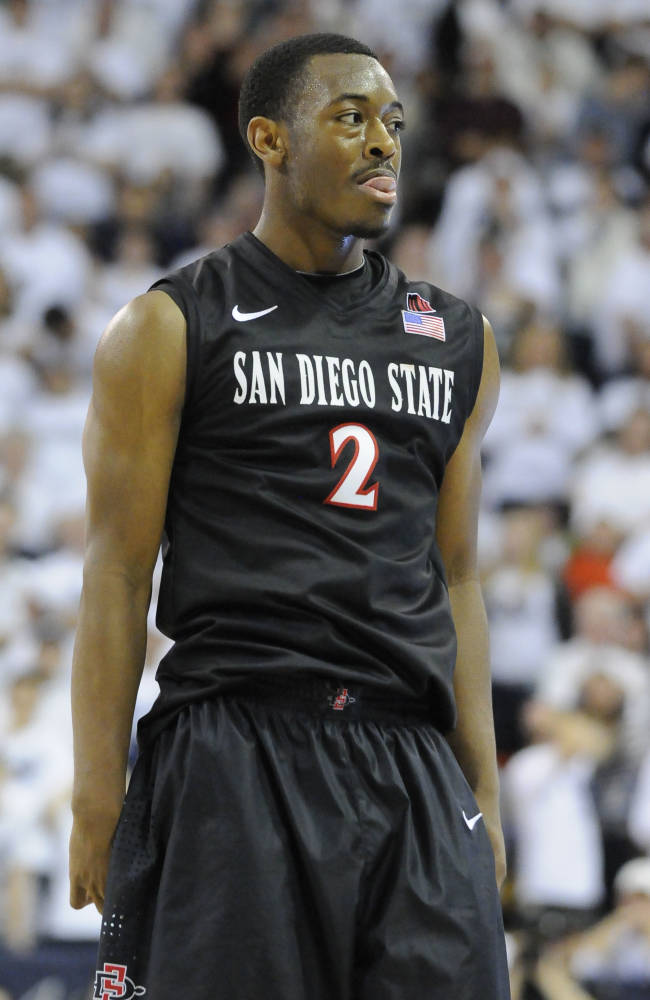 San Diego State guard Xavier Thames (2) smiles to his teammates after hitting a three pointer in overtime of an NCAA college basketball game Saturday, Jan. 25, 2014, in Logan, Utah