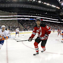 The puck bounces up as New Jersey Devils center Travis Zajac (19) and New York Islanders left wing Nikolay Kulemin (86), of Russia, chase after it during the second period of an NHL hockey game, Friday, Jan. 9, 2015, in Newark, N.J The Associated Press
