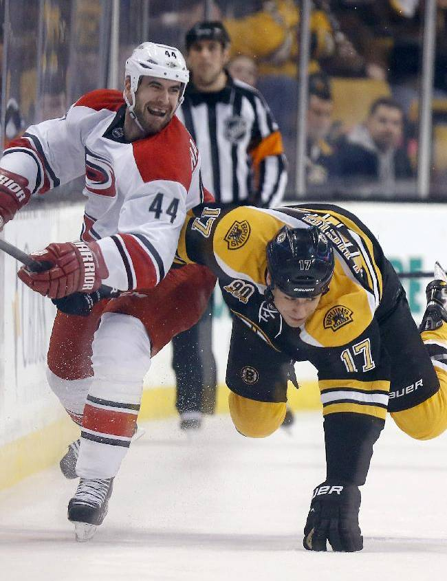 Carolina Hurricanes' Jay Harrison (44) checks Boston Bruins' Milan Lucic (17) in the first period of an NHL hockey game in Boston, Saturday, March 15, 2014