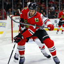 Chicago Blackhawks defenseman Niklas Hjalmarsson (4) goes after the puck while being hooked by Carolina Hurricanes center Riley Nash during the first period of an NHL hockey game in Chicago, Friday, March 21, 2014 The Associated Press
