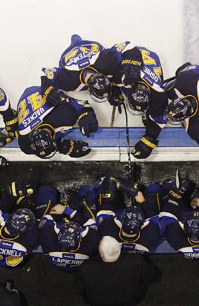 St. Louis Blues head coach Ken Hitchcock, bottom center, gathers his players together during a timeout after the Chicago Blackhawks took a 3-2 lead in the third period of Game 2 of a first-round NHL hockey playoff series on Saturday, April 19, 2014, at the Scottrade Center in St. Louis